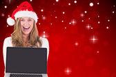 Festive blonde showing a laptop — Stock Photo