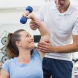Personal trainer helping client lift dumbbell — Stock Photo #56903993