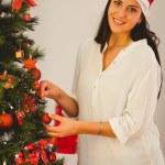 Woman hanging christmas decorations on tree — Stock Photo #56904031
