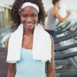 Pretty woman smiling at camera beside treadmills — Stock Photo #56904163