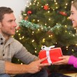 Sitting couple giving each other presents — Stock Photo #56904621