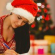 Festive brunette writing her list — Stock Photo #56904961