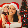 Festive mother and daughter smiling at camera — Stock Photo #56905161