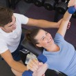 Personal trainer helping client lift dumbbells — Stock Photo #56905367