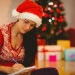 Festive brunette writing her list — Stock Photo #56905391