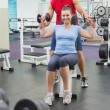 Personal trainer helping client lift dumbbells — Stock Photo #56905965