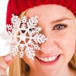 Festive blonde holding snowflake decoration — Stock Photo #56906317