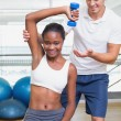 Personal trainer helping client lift dumbbell — Stock Photo #56906383