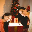 Festive mother and daughter opening a glowing christmas gift — Stock Photo #56907637