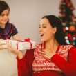 Daughter giving her mother a christmas present — Stock Photo #56909075