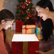 Festive mother and daughter opening a glowing christmas gift — Stock Photo #56909413