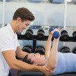 Personal trainer helping client lift dumbbells — Stock Photo #56909721