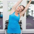 Fit brunette warming up in fitness studio — Stock Photo #56909835
