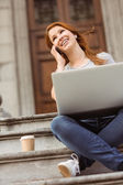 Smiling girl calling with her mobile phone and using laptop — Stock Photo