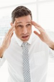Young businessman with severe headache in office — Stock Photo