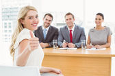 Woman gesturing thumbs up in front of corporate personnel officers — Stock Photo