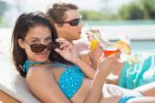 Couple with drinks by swimming pool — Fotografia Stock