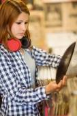 Redhead with a headphone around the neck holding a vinyl — Stock Photo