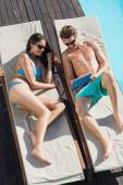 Couple using digital tablet on sun loungers — Stock Photo