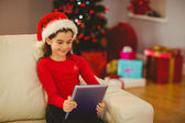 Festive little girl using tablet pc on couch — Stock Photo