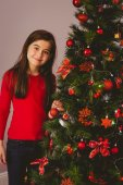 Little girl smiling at camera beside christmas tree — Stock Photo