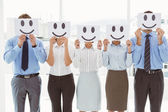 Business people holding happy smileys on faces — Stock Photo