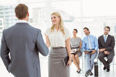 Businesspeople in front of people waiting for interview — Stock Photo
