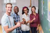 Creative business people gesturing thumbs up by blackboard — Stock Photo