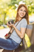 Pretty redhead holding her camera — Stock Photo