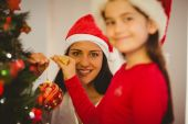 Mother and daughter hanging christmas decorations on tree — Stock fotografie