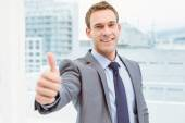 Businessman gesturing thumbs up in office — Stock Photo