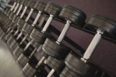 Heavy black dumbbells on rack in weights room — Foto Stock