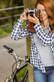 Young redhead taking a picture leaning against a tree — Stock Photo