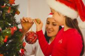 Mother and daughter hanging christmas decorations on tree — Stock Photo