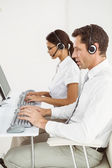 Business people with headsets using computers in office — Stock Photo
