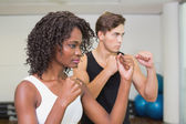 Fit couple standing with fists raised — Stock Photo