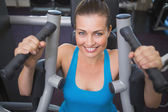 Fit brunette using weights machine for arms — Stock Photo
