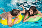 Couple in inflatable rings at swimming pool — Stock Photo
