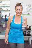 Fit brunette smiling at camera in fitness studio — 图库照片