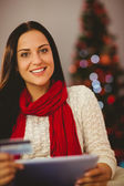 Pretty brunette shopping online with tablet at christmas — Stock Photo