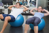 Couple doing sit ups on exercise balls — Stock Photo