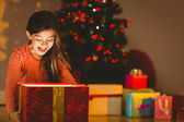 Little girl opening a glowing christmas gift — Stock Photo