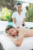 Handsome man receiving stone massage — Stock Photo