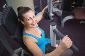 Morena ajuste utilizando la máquina de pesas para brazos — Foto de Stock