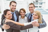 Business people with arms around in office — Stock Photo