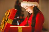 Festive little girl opening a glowing christmas gift — Stock Photo