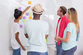 Creative team clapping hands by sticky notes on wall — Stock Photo