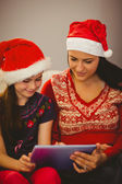 Festive mother and daughter using tablet pc — Stock Photo
