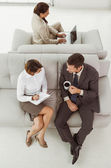 Young business people on couch — Stock Photo
