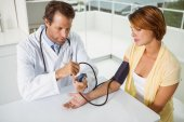Doctor checking blood pressure of woman at medical office — Stock Photo